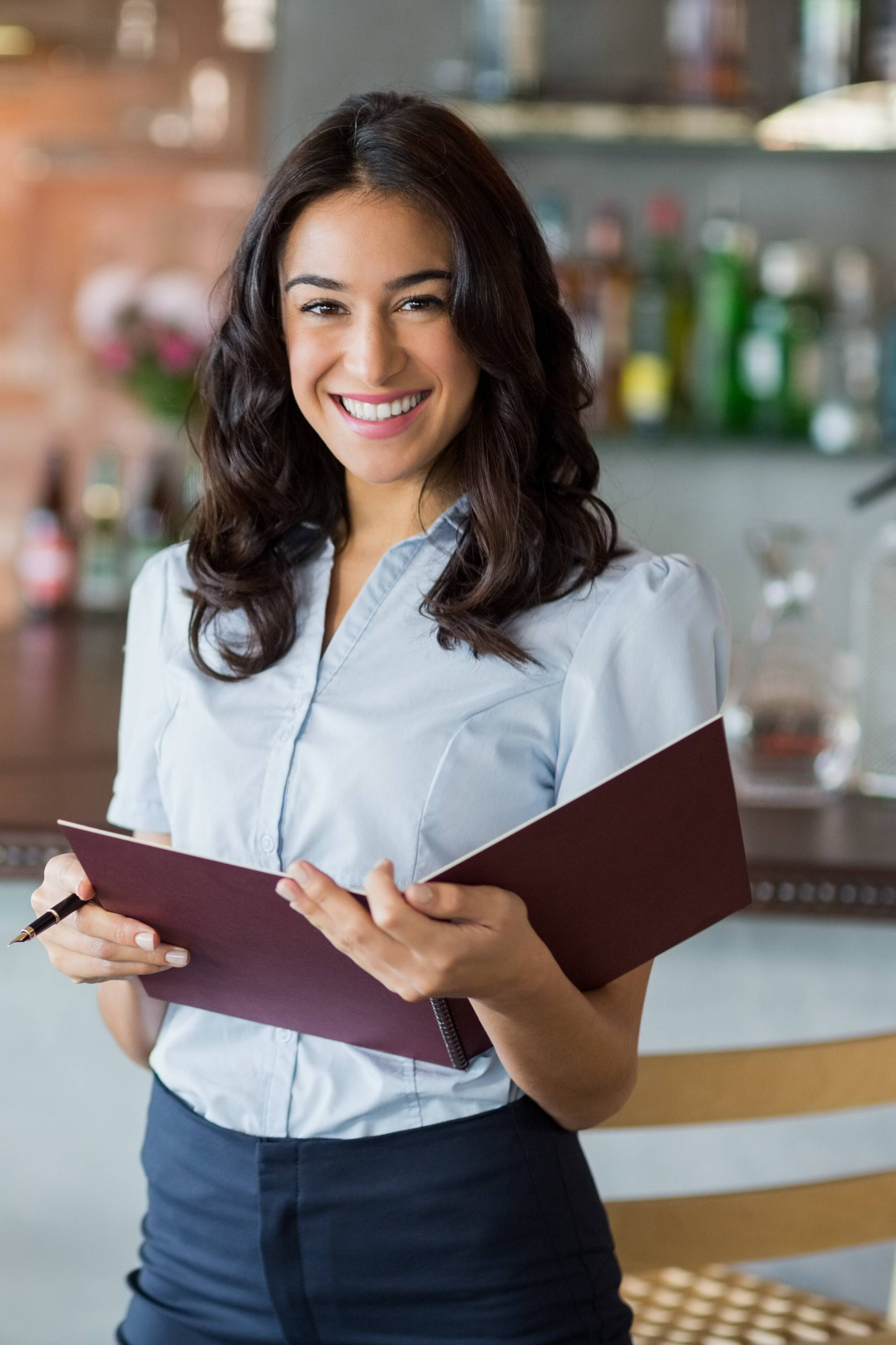 Restaurant manager standing in front of bar